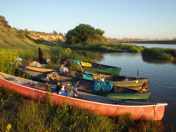 Canoes parked on the riverbank.