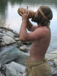 Student in Buckskins drinking from gourd.